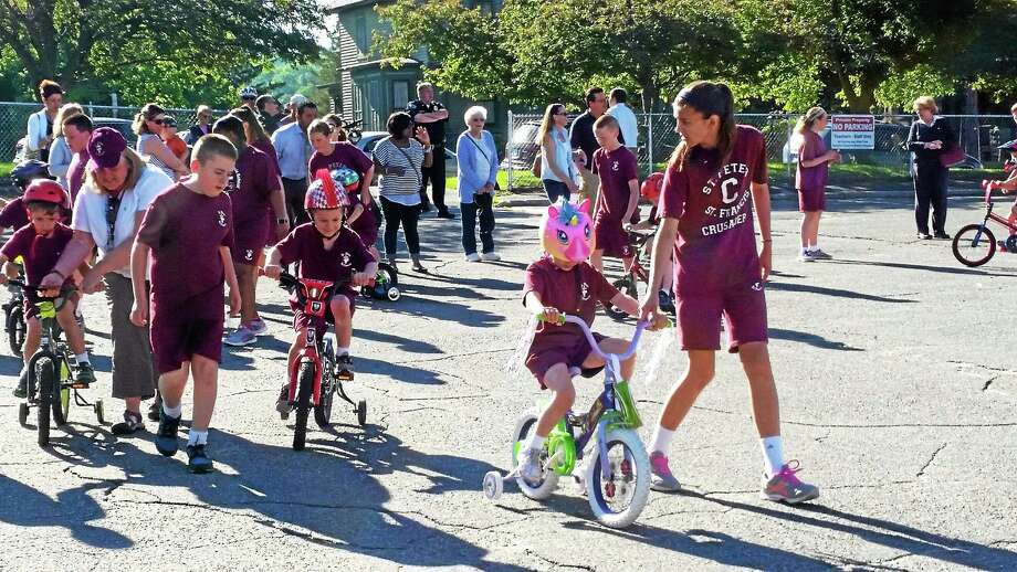 Students at St. Peter/St. Francis School rode their bikes in the school's parking lot on Friday to encourage Fr. Jim Sullivan in his charitable ride to Maryland. Photo: Amanda Webster — The Register Citizen