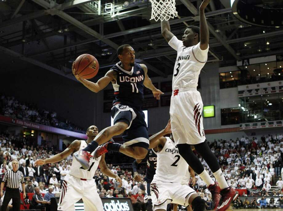 UConn guard Ryan Boatright (11) passes under the basket against Cincinnati forward Shaquille Thomas (3) in the second half Thursday. Photo: Frank Victores — The Associated Press  / FR170726 AP