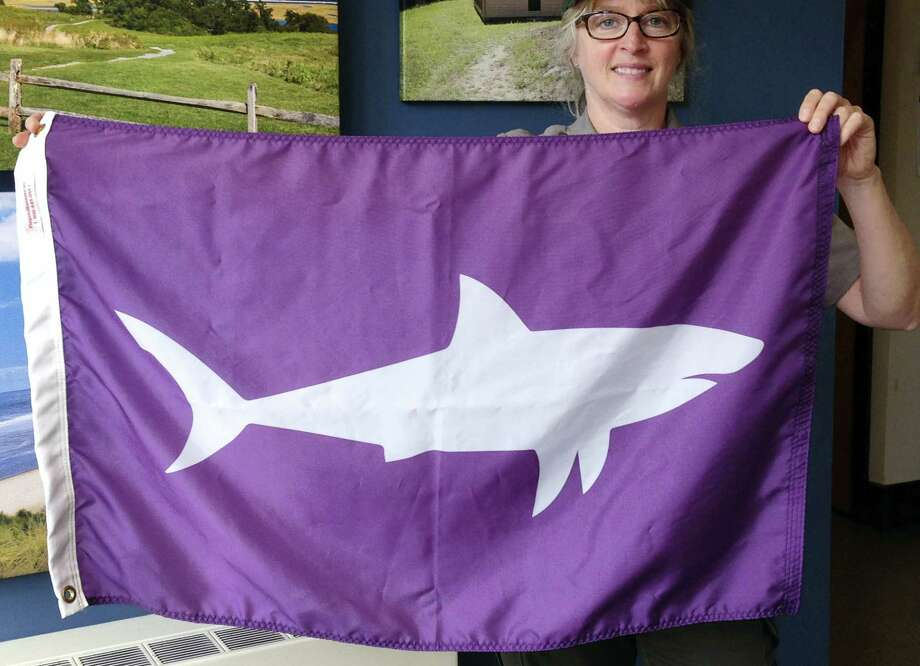 In this Wednesday, May 25, 2016, photo, Leslie Reynolds, chief ranger at the Cape Cod National Seashore, displays a shark-alert flag at the U.S. Parks Service's Cape Cod headquarters in Wellfleet, Mass. The new flags will be used to warn beachgoers to avoid going in the water at areas where sharks have been sighted. Photo: AP Photo/Philip Marcelo  / Copyright 2016 The Associated Press. All rights reserved. This material may not be published, broadcast, rewritten or redistribu