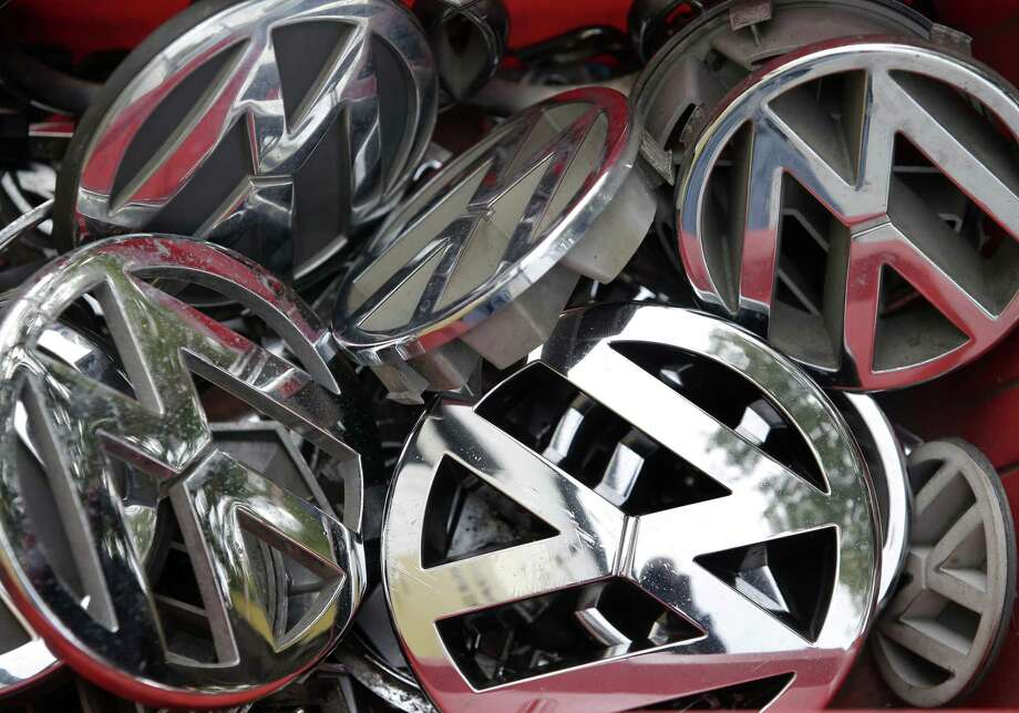 In this Sept. 23, 2015 photo, company logos of the German car manufacturer Volkswagen sit in a box at a scrap yard in Berlin, Germany. Who knew about the deception, when did they know it and who directed it? Those are among questions that state and federal investigators want answered as they plunge into the emissions scandal at Volkswagen that has cost the chief executive his job, caused stock prices to plummet and could result in billions of dollars in fines. Photo: AP Photo/Michael Sohn, File  / AP