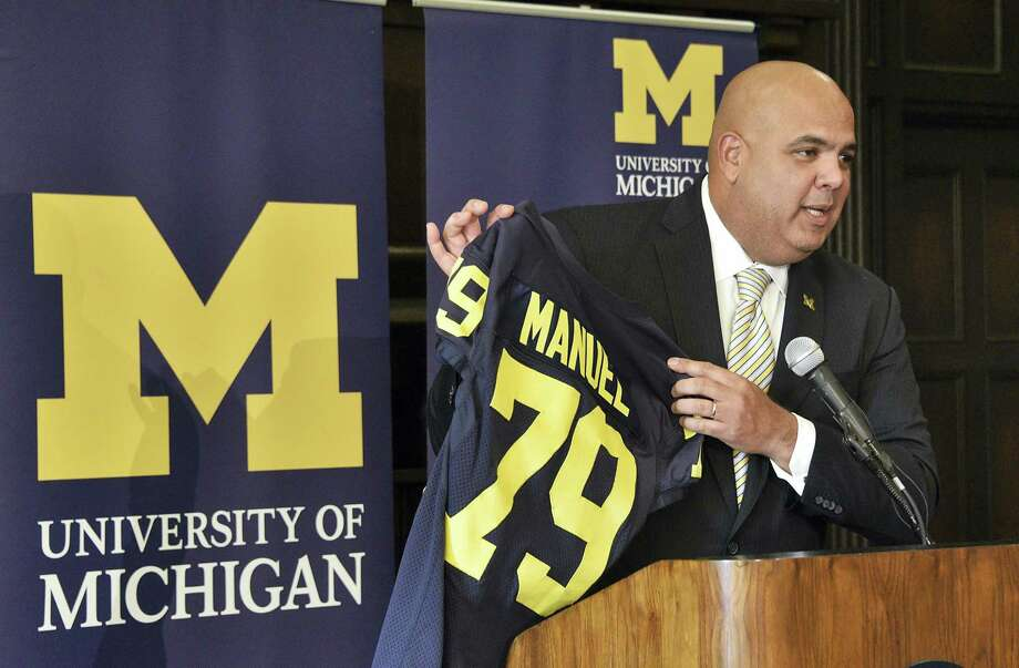 Michigan's new athletic director Warde Manuel holds up a jersey during a news conference Friday at the Student Union in Ann Arbor, Mich. The 47-year-old Manuel, who had been UConn's athletic director since 2012, was given a five-year deal by Michigan. Photo: Detroit News — Via The AP  / Detroit News