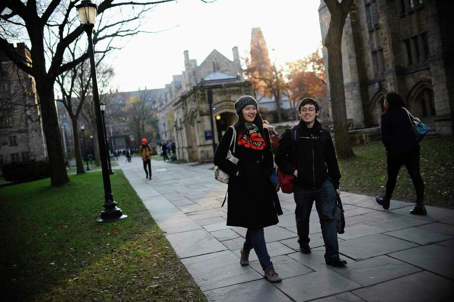 In this Nov. 20, 2014 photo, Yale University sophomore Yupei Guo, left, walks with friend Joseph Lachman on the school's campus in New Haven, Conn. With more undergraduates coming from overseas than ever, some Ivy League universities are reaching out in new ways to attract international students of more varied backgrounds -- and particularly from China, which sends more students to the U.S. than any other country. Photo: AP Photo/Jessica Hill  / FR125654 AP