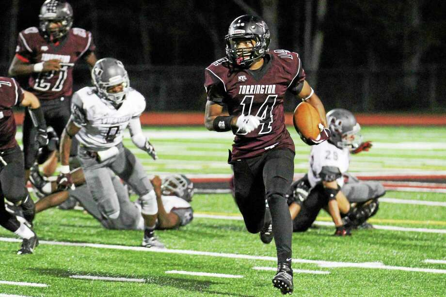 Torrington's Newton Frias gains some yardage in his teamís win over Naugatuck Friday night. Photo: Marianne Killackey — Special To Register Citizen  / 2015