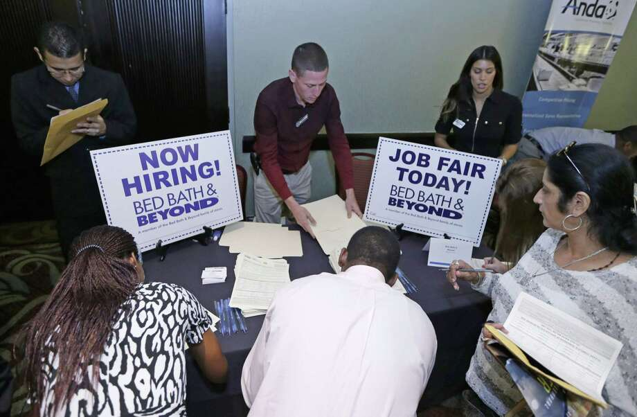 FILE - In this Oct. 22, 2014 file photo, job seekers fill out a job applications at a Bed Bath and Beyond table at a job fair in Miami Lakes, Fla.  The U.S. Labor Department reports on the number of people who applied for unemployment benefits for the week ending Jan. 3, 2015 on Thursday, Jan. 8, 2015. (AP Photo/Alan Diaz, File) Photo: AP / AP