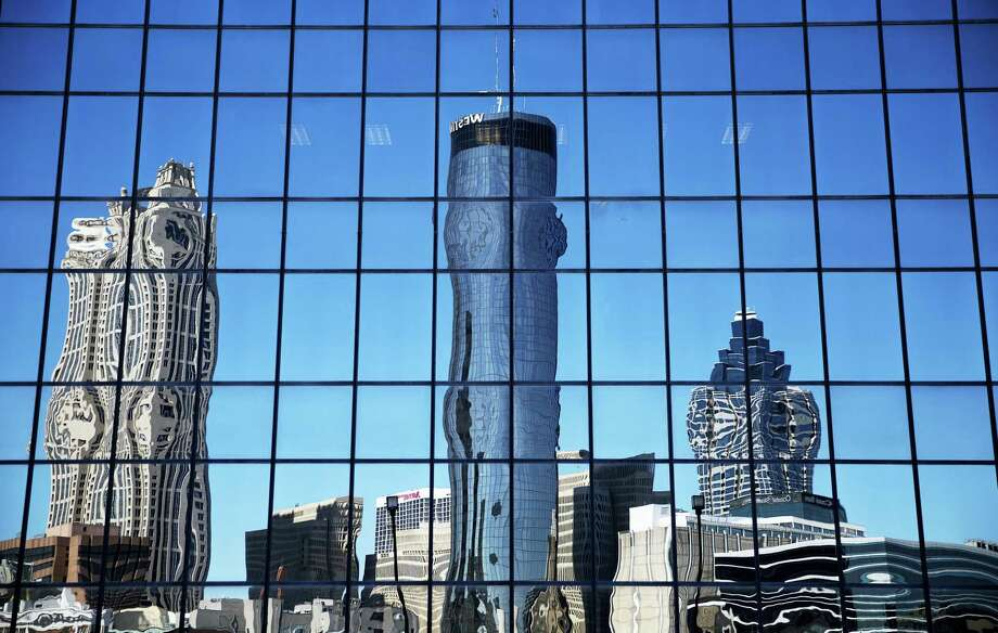 The Westin hotel, center, is reflected along with other downtown buildings in the windows of an office tower in Atlanta, Wednesday, Sept. 28, 2016. An exit button inside the Westin hotel where a worker was found dead failed to work during an inspection, trapping multiple people who had to beat on the door to alert someone to let them out, a medical examiner found. The Fulton County Medical Examiner's Office has amended its autopsy for Carolyn Mangham to include the new details about the freezer exit button at the Westin Peachtree Plaza. Photo: AP Photo/David Goldman   / Copyright 2016 The Associated Press. All rights reserved.