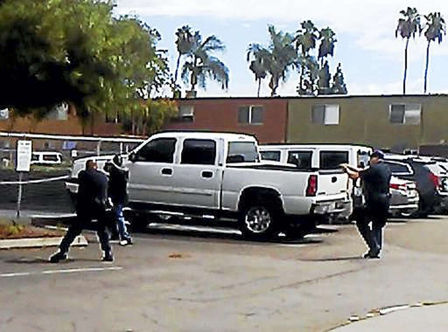"In this Tuesday, Sept. 27, 2016, frame from video provided by the El Cajon Police Department, a man, second from left, faces police officers in El Cajon, Calif. The man reportedly acting erratically at a strip mall in suburban San Diego was shot and killed by police after pulling an object from his pocket, pointing it at officers and assuming a ""shooting stance,"" authorities said. Some protesters claimed the man was shot with his hands raised, but police disputed that and produced the frame from cellphone video taken by a witness that appeared to show the man in the ""shooting stance"" as two officers approached with weapons drawn. Photo: El Cajon Police Department Via AP   / El Cajon Police Department"