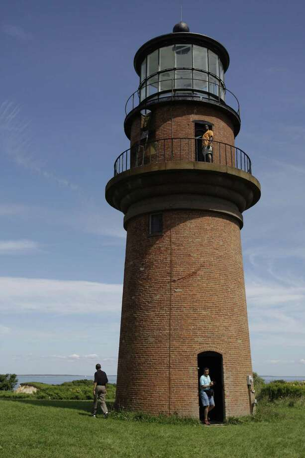 FILE - In this Aug. 27, 2009, file photo, President Barack Obama, left, walks around Gay Head Lighthouse while on vacation on Martha's Vineyard in Aquinnah, Mass. The Gay Head Lighthouse, a 160-year-old beacon thatís among the most endangered historic landmarks in the United States, is expected to begin a multi-day trek inland from its rapidly eroding cliffside perch on Thursday, May 28, 2015. (AP Photo/Alex Brandon, File) Photo: AP / AP