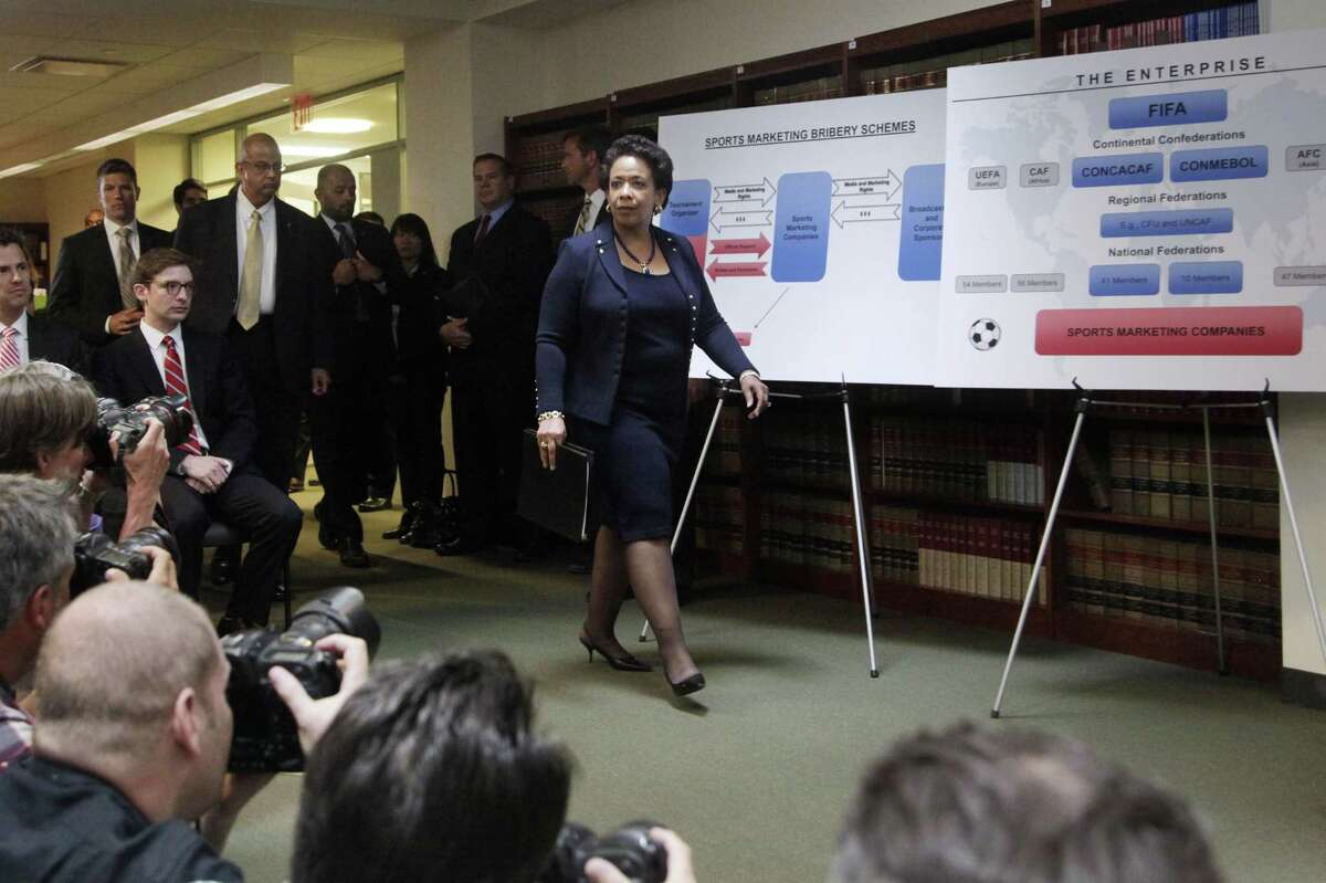 Attorney General Loretta E. Lynch, center, arrives for a news conference to announce an indictment against nine FIFA officials and five corporate executives for racketeering, conspiracy and corruption on Wednesday in the Brooklyn borough of New York.