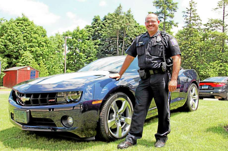 Officer Steven Cloutier stands next to his 2011 Chevy Camaro outside the Torrington Police Department on June 19, 2013. Photo: Register Citizen File Photo