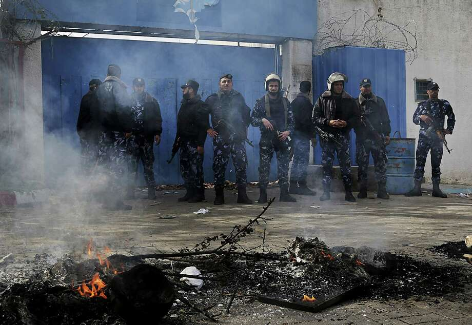 Palestinian riot police stand guard in front of the offices of the United Nations Special Coordinator for the Middle East Peace Process (UNSCO) during a protest against the decision of the U.N. Relief and Works Agency to suspended an aid program for Gaza residents displaced by the last summer's war, in Gaza City, in the northern Gaza Strip, Wednesday, Jan. 28, 2015. Dozens of Palestinians attacked a United Nations compound in Gaza City following the world body's suspension of an aid program for victims of last year's war. (AP Photo/Adel Hana) Photo: AP / AP