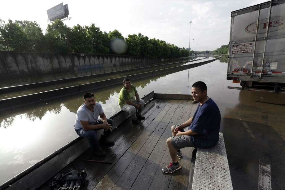 Stranded motorists wait for floodwaters to recede on Interstate 45 after heavy rains overnight in Houston Tuesday. Photo: Associated Press  / AP