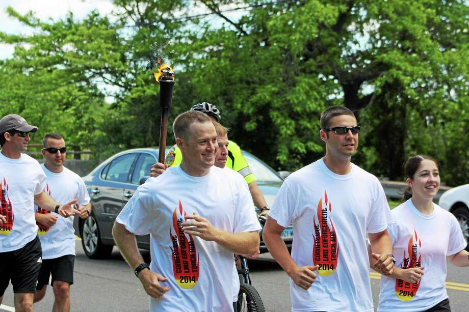 With Guilford Officer Rich Casey holding up the torch, fellow town officers run for Special Olympics in this 2014 photo. Photo: NEW HAVEN REGISTER File Photo