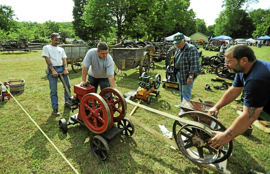 Setting up a 1921 two-horsepower economy engine are, from left, Bill Brague of Warren, Donald Cherico of New Milford, Ron Orlando of Sharon, and Bryan McBreairty. Photo: John Fitts — The Register Citizen