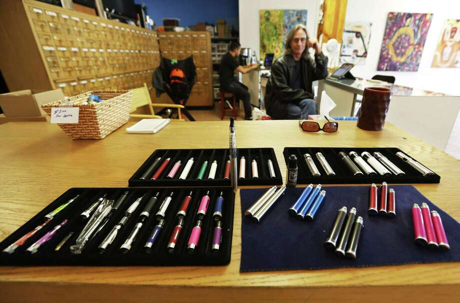 FILE - In this Dec. 4, 2013, file photo, John Hartigan, right, proprietor of Vapeology LA, sits behind an array of electronic cigarettes at his store in Los Angeles. A California state lawmaker has introduced legislation Tuesday, Jan. 27, 2015, that would ban the use of increasingly popular electronic cigarettes in public spaces. The bill by Sen. Mark Leno, D-San Francisco, would classify the devices that heat liquid nicotine into vapor as tobacco products similar to cigarettes. That would prohibit Californians from using the devices in restaurants, buses, hospitals and other places they cannot smoke. (AP Photo/Reed Saxon, File) Photo: AP / AP