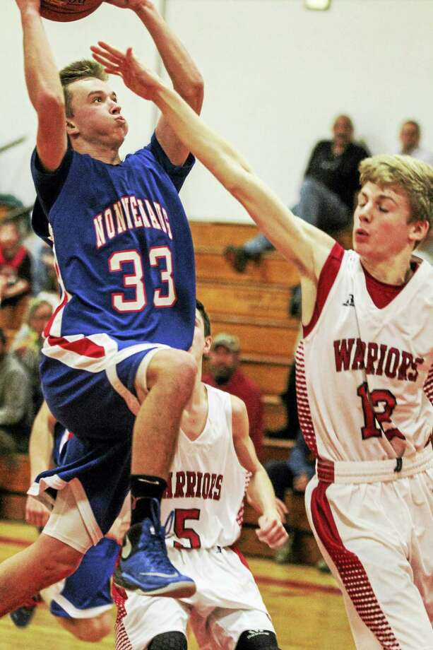 Nonnewaug's Nate Firlings soars over talented Wamogo freshman Garrett Sattazahn on the way to his game-high 14 points for the night. Photo: Marianne Killackey — The Register Citizen  / 2015