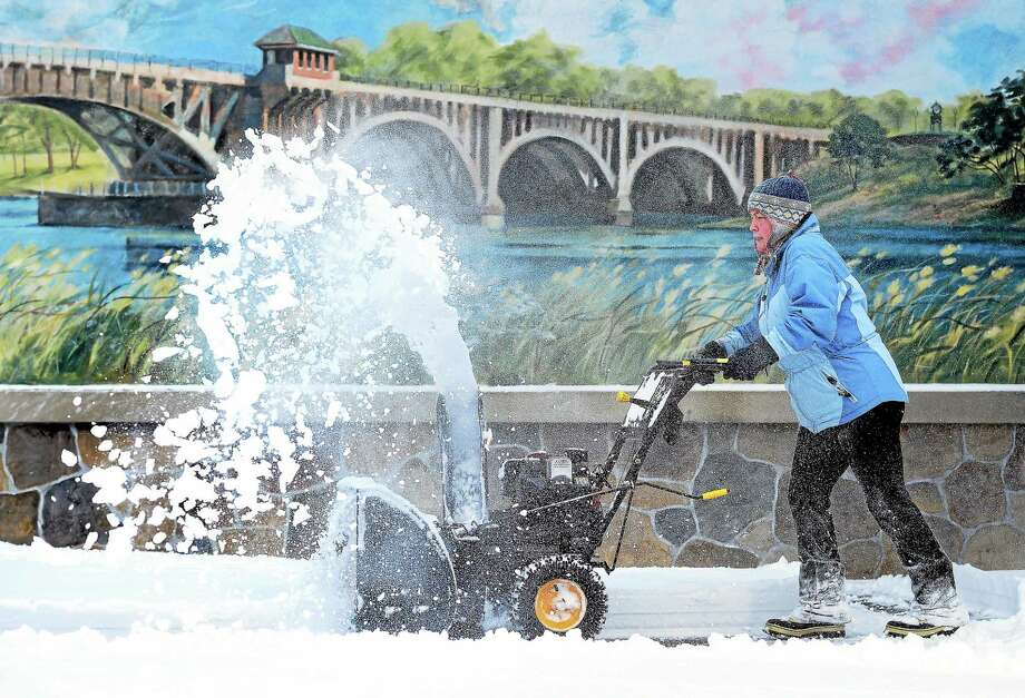 Nanci Micha clears the snow from the parking lot of the Bridge House Restaurant in Milford on January 27, 2015.  Behind her is a mural of the Washington Bridge connecting Stratford with Milford over the Housatonic River. Photo: (Arnold Gold — New Haven Register)