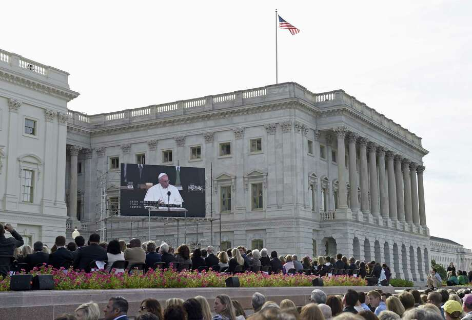 People watch Pope Francis on a large screen television from the West Front of the Capitol in Washington, Thursday, Sept. 24, 2015, as the pope speaks inside before a joint meeting of Congress. Pope Francis is the first pontiff in history to speak before a joint meeting of Congress. Photo: AP Photo/Susan Walsh   / AP
