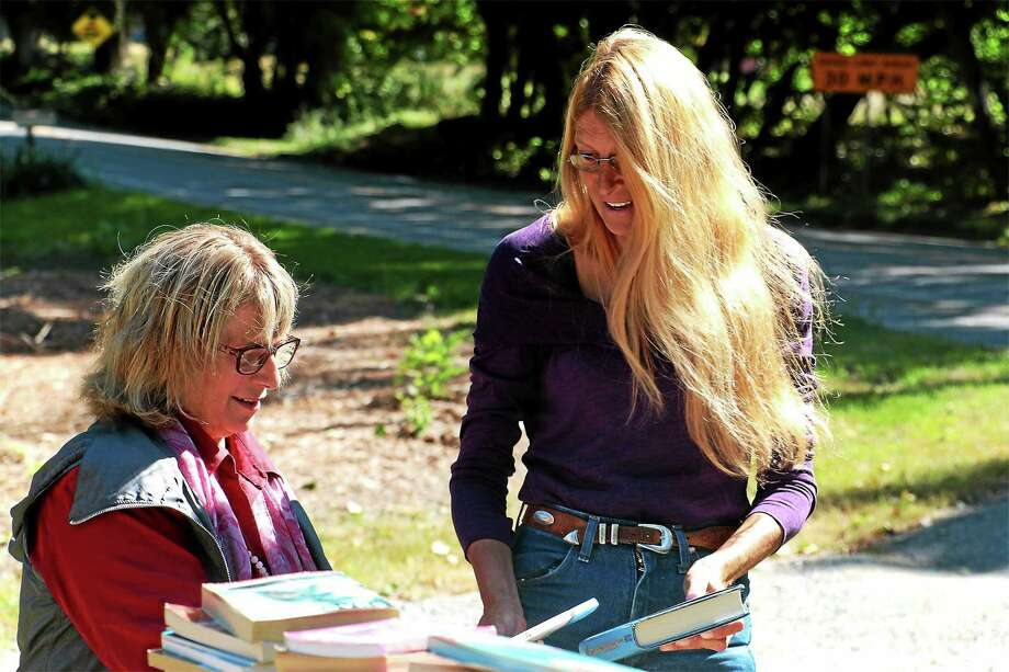 Rose Buckens, left, accepts some book donations from fellow Morris reident Tracy Martin. Photo: John Fitts — THe Register Citizen