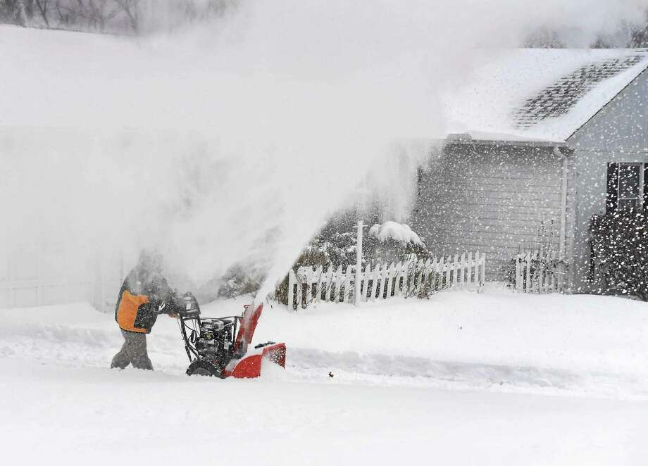 (Peter Hvizdak - New Haven Register) Jen Hanrahan uses a snowblower to clear her driveway on Pine Orchard Road in Branford, Conn., at 21F degrees, with gusty winds from the North at 20-mph, which feels like 1F degrees Tuesday, January 27, 2015. Photo: ©2015 Peter Hvizdak / ©2015 Peter Hvizdak