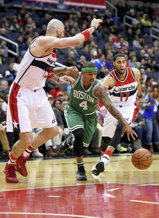 Boston Celtics guard Isaiah Thomas (4) dribbles between Washington Wizards center Marcin Gortat, left, of Poland, and guard Garrett Temple (17) during the second half of an NBA basketball game, Monday, Jan. 25, 2016, in Washington. The Celtics won 116-91. (AP Photo/Nick Wass) Photo: AP / FR67404 AP