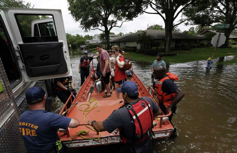 Members of the Houston and Webster Fire departments help residents evacuate through the floodwaters surrounding their homes in Houston Tuesday. Heavy rain overnight caused flooding and closure of sections of highways in the Houston area. Photo: Associated Press  / AP