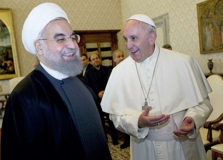 Pope Francis and Iranian President Hassan Rouhani, left, share a laugh during their private audience at the Vatican on Jan. 26, 2016. Iran's president has paid a call on Pope Francis at the Vatican during a European visit aimed at positioning Tehran as a potential top player in efforts to resolve Middle East conflicts, including Syria's civil war. Photo: AP Photo/Andrew Medichini, Pool  / AP
