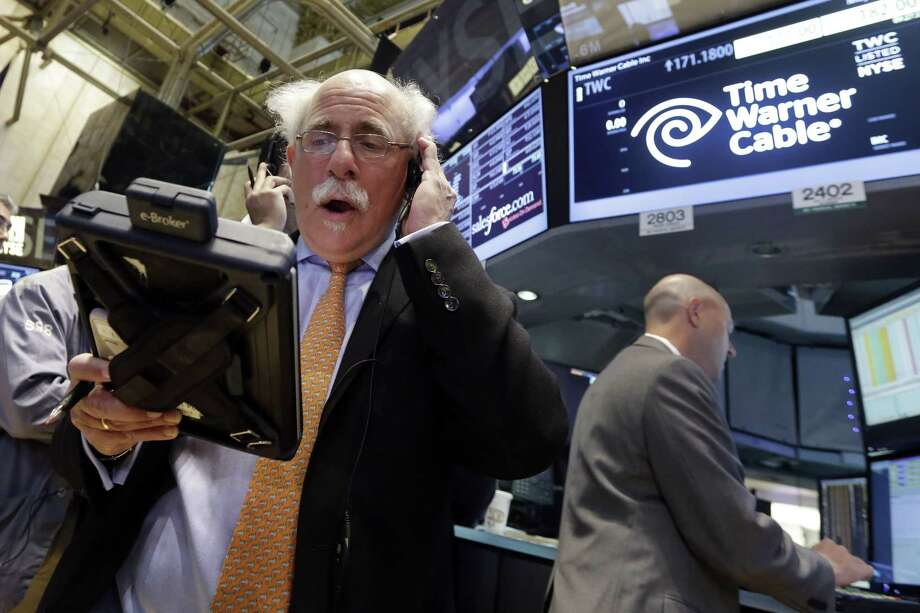Trader Peter Tuchman, left, works the post that handles Time Warner Cable on the floor of the New York Stock Exchange Tuesday. Photo: Richard Drew — The Associated Press  / AP