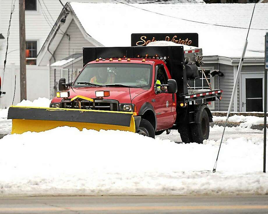 "A town of Branford Public Works truck clears old snow and drops snow melt in the public parking lot on South Main Street and Montowese Ave. in Branford as the town prepares for the blizzard blast in Connecticut Monday morning, January 25, 2015. Photo: Peter Hvizdak -- New Haven Register  / ""©2015 Peter Hvizdak"""