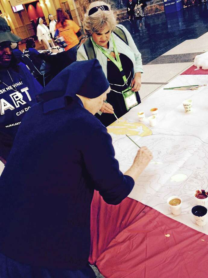 Sister Christene Papavero of San Jose, Calif. and Jean Martinelli of North Muskegon, Mich. help paint the mural being made at the Philadelphia Convention Center especially for the World Meeting of Families and the Pope Francis visit. Photo: Kathleen E. Carey — Daily Times