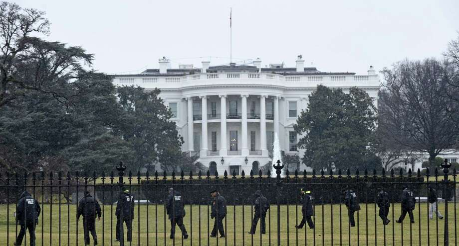 Secret Service officers search the south grounds of the White House in Washington on Jan. 26, 2015. An unmanned aerial drone was found on the White House grounds during the middle of the night while President Barack Obama and the first lady were in India, but his spokesman said Monday that it posed no threat. Photo: AP Photo/Susan Walsh  / AP