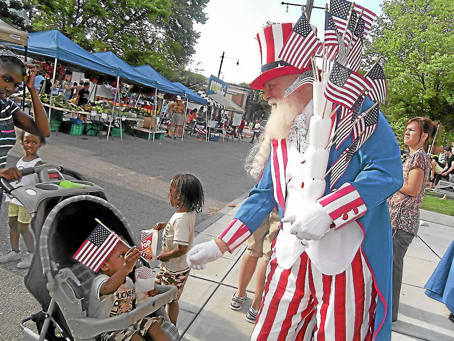 """""""Uncle Sam"""" passes out American flags during a 2012 Main Street Marketplace event in Torrington. Photo: Register Citizen File Photo"""
