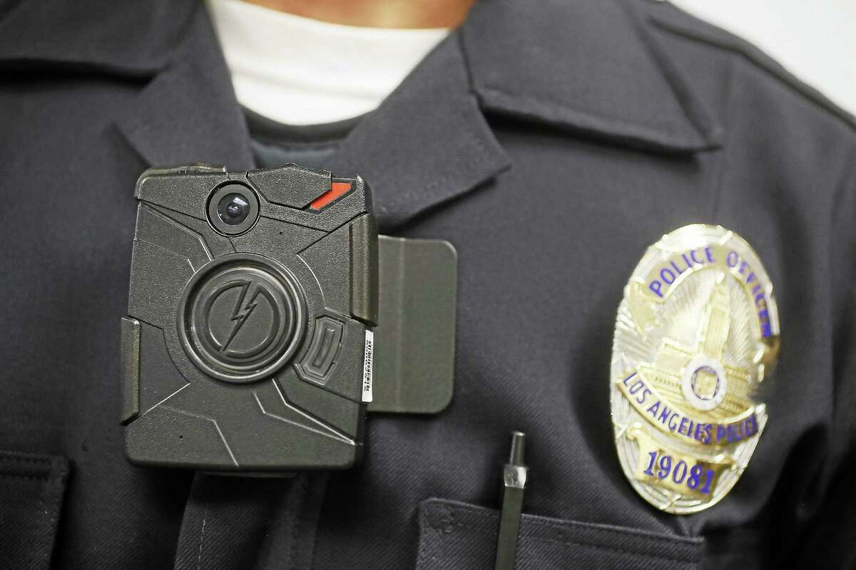 """In this Jan. 15, 2014 photo, a Los Angeles Police officer wears an on-body camera during a demonstration for media in Los Angeles. The fatal police shooting of the unarmed black teenager in Ferguson, Mo. has prompted calls for more officers to wear so-called """"body cameras,"""" simple, lapel-mounted gadgets that record the interactions between the public and law enforcement."""