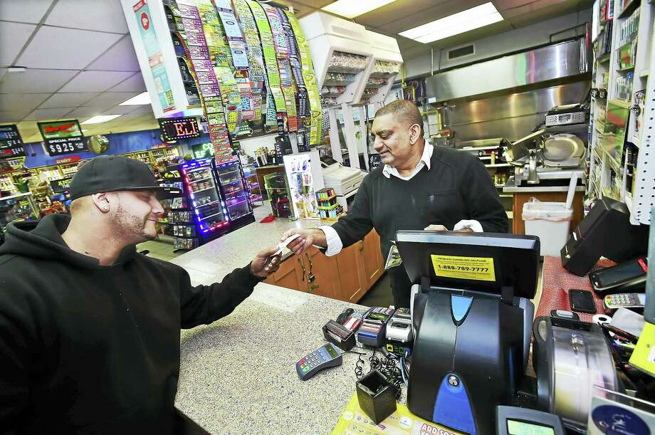 Nick Sarwar, who owns S&B Food Mart & Deli with his wife, Samina Bashir, hands a Powerball ticket to Billy Revis of New Haven Thursday night. Photo: Catherine Avalone — New Haven Register   / New Haven RegisterThe Middletown Press
