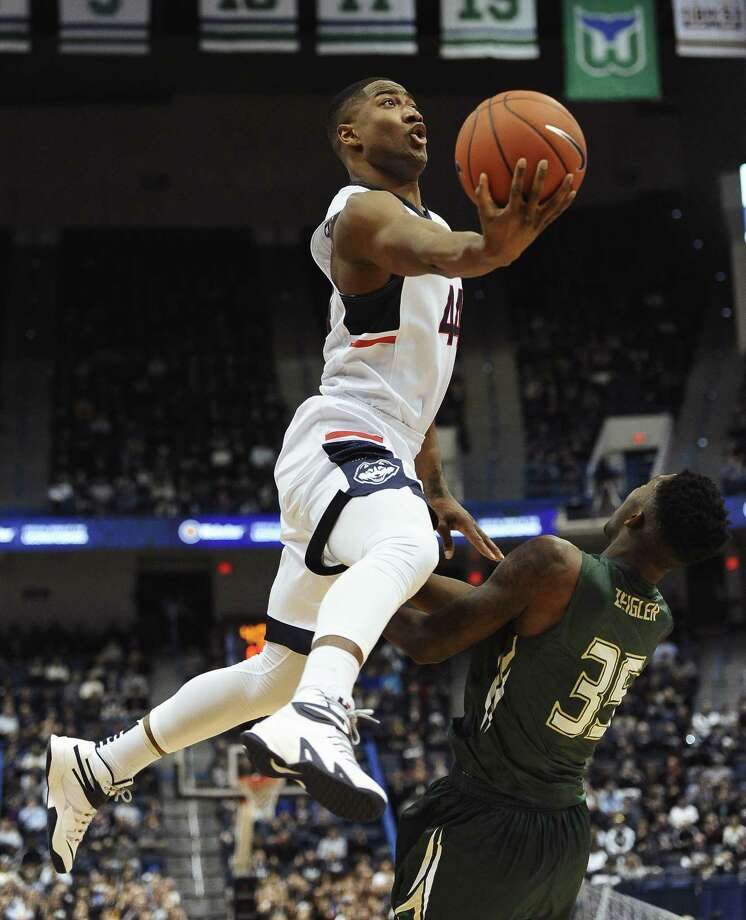 UConn's Rodney Purvis, left, shoots over South Florida's Bo Zeigler during the first half Sunday. Photo: Jessica Hill — The Associated Press  / FR125654 AP