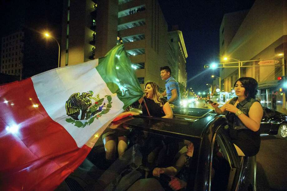 In this May 24, 2016, photo, a woman waves the Mexican flag while driving past the Albuquerque Convention Center after a rally by Republican presidential candidate Donald Trump in Albuquerque, N.M. Hispanic voters in Florida, New Mexico and California have waved Mexican flags and bashed Donald Trump piñatas to protest the Republican presidential contender's hard line approach to immigration. Yet far from the protests, an increasingly vocal Hispanic minority is speaking out in favor of the brash billionaire. Photo: Jett Loe/The Las Cruces Sun-News Via AP   / The Las Cruces Sun-News
