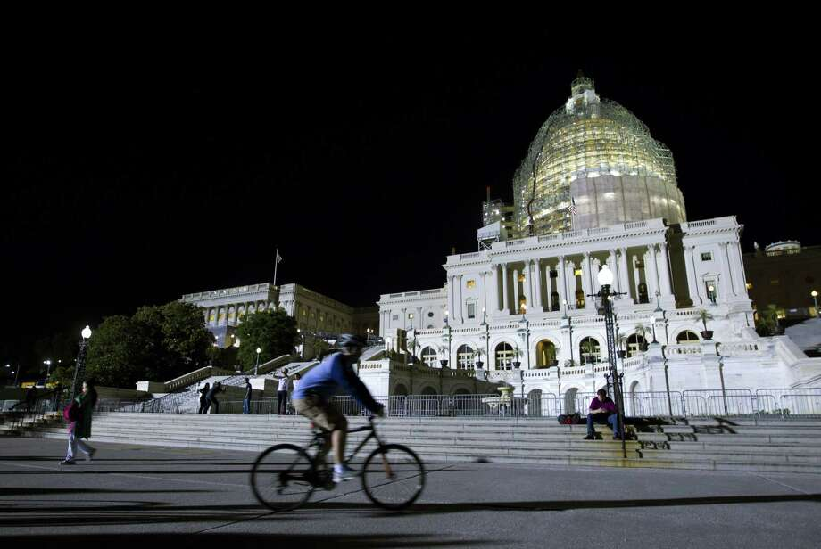 The U.S. Capitol is illuminated at night as the Senate continues to work late on May 22, 2015 on Capitol Hill. When senators left town early Saturday after approving a brief extension of the nation's highway and transit aid, they were following a well-worn path. Photo: AP Photo/Jose Luis Magana  / FR159526 AP