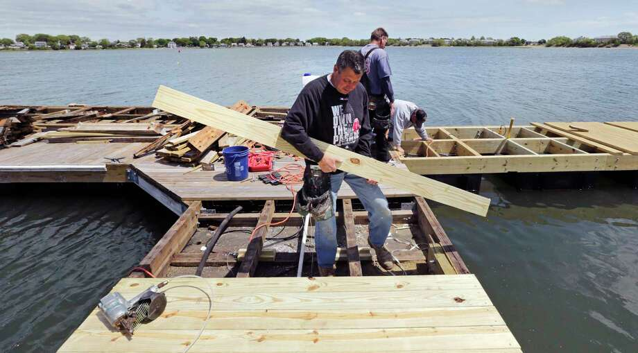 In this May 20, 2015 photo, carpenter Rick Nelson, of Brockton, Mass., installs a new deck plank on a dock heavily damaged during this past winter at the Bay Pointe Marina in Quincy, Mass. The deep freeze that gripped the Northeast this past season dealt a severe blow to marinas and yacht clubs: Ice snapped pilings in half, shredded wooden docks and left behind wreckage that many compare to the effects of a hurricane. Bay Pointe Marina suffered over $1 million in damage from this past winter's storms. Photo: AP Photo/Charles Krupa  / AP
