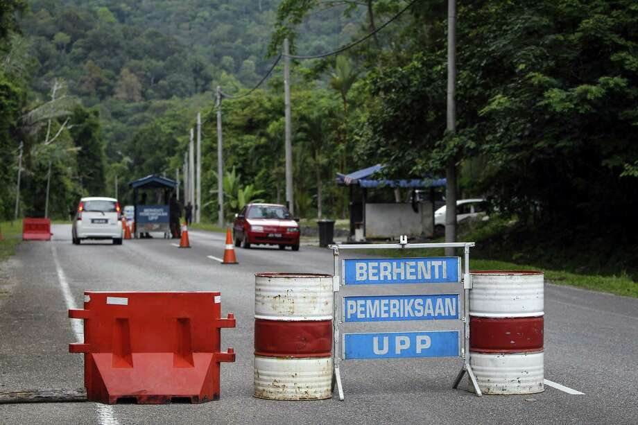 """A check point is seen at the entry point to Malaysia - Thailand border in Wang Kelian, Malaysia on May 24, 2015. Malaysian authorities said Sunday that they have discovered graves in more than a dozen abandoned camps used by human traffickers on the border with Thailand, where Rohingya Muslims fleeing Myanmar have been held. The blue signs read, from top, """"Stop,"""" """"Inspection,"""" and """"UPP (Anti-Smuggling Unit)."""" Photo: AP Photo/Joshua Paul  / AP"""