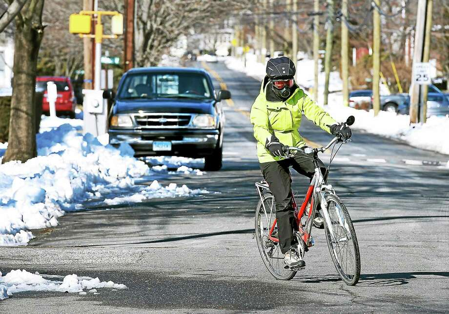 Mary Cavallo bundles up against the cold dry air during her bicycle ride along the shoreline in Milford on Sunday. Cavallo bicycles about four times per week but Tuesday won't be one of those days. Photo: Arnold Gold — New Haven Register