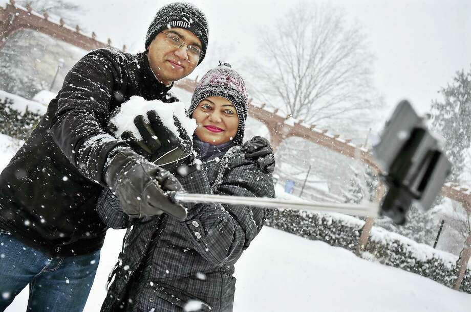 Transplants from India, Bhaskar Sengupta, a research scientist at Yale University and his wife Kheya Chakravarty, take a selfie in the snow on Trumbull Street in New Haven during the winter storm on Saturday, January 23, 2016. Photo: Catherine Avalone — New Haven Register  / New Haven RegisterThe Middletown Press
