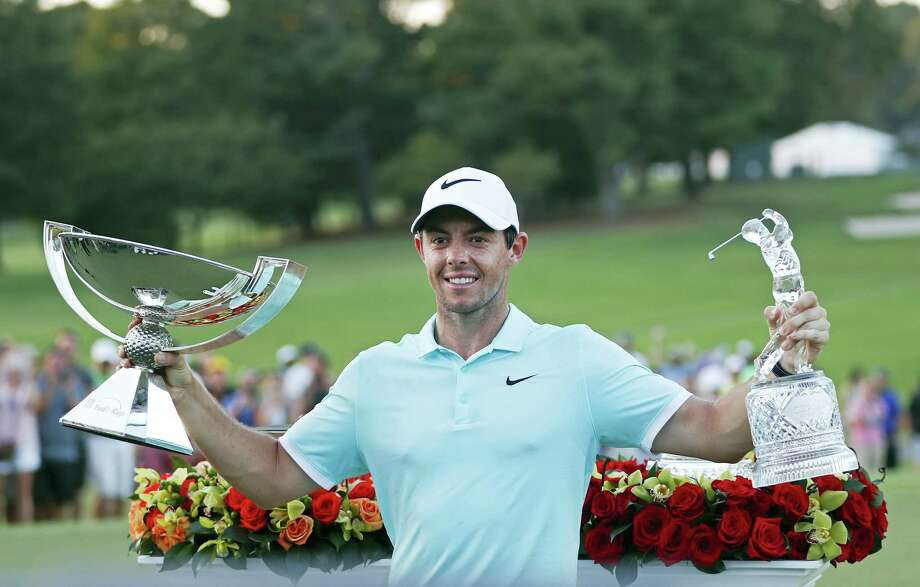 Rory McIlroy poses with the trophies after winning the Tour Championship and FedEX Cup on Sunday. Photo: John Bazemore — The Associated Press  / Copyright 2016 The Associated Press. All rights reserved.