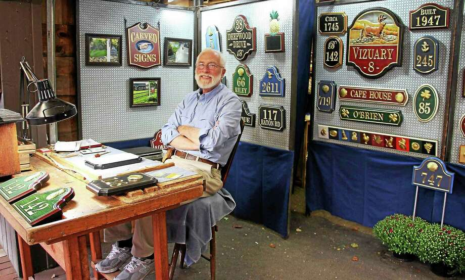 East Canaan resident Joe Cieslowski, creator of hand-carveds signs and gifts, at his booth in Craft Commons at the Big E in West Springfield, Mass. Photo: Manon L. Mirabelli — The Register Citizen