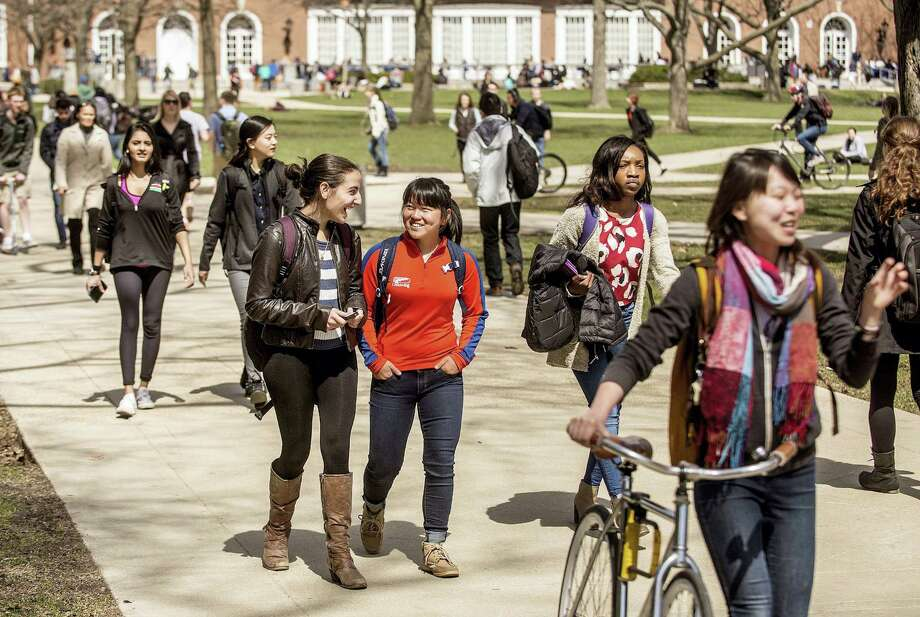 In this Oct. 28, 2015 photo, students walk across the Quad on the University of Illinois campus in Urbana, Ill. College tuition may be daunting, but so are the conversations about how to pay for it. Experts say it pays off for parents talk with children early and often about how to cover higher education costs. Photo: Heather Coit/The News-Gazette Via AP  / The News-Gazette