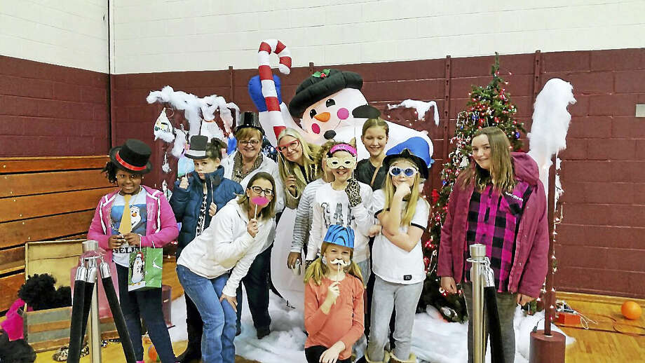 Volunteer organizer Melissa Bird (center) and students from the St. Peter/St. Francis School posed in festive costumes and masks at the School's 10th annual Winter Wonderland fair in Torrington on Saturday afternoon. The event attracted an estimated 175 visitors for face-painting, games, popcorn, homemade baked goods and an ugly sweater contest, raising about $1,800 for the school despite the threat of a blizzard. Photo: Photo By N.F. Ambery