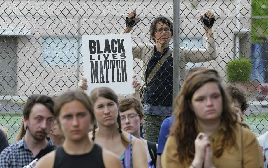 People gather inside and outside a fence Thursday, May 21, 2015, during a rally at a park in Olympia, Wash. Two stepbrothers suspected of trying to steal beer from a grocery store were shot early Thursday by a police officer after he confronted them and reported he was being assaulted with a skateboard. Both men are expected to survive. (AP Photo/Ted S. Warren) Photo: AP / AP
