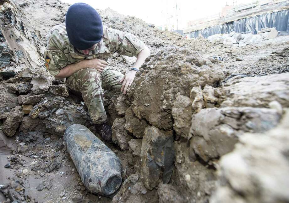 An army bomb disposal expert inspects an unexploded World War II bomb found in Wembley, north London, Thursday May 21, 2015. The 50-kilogram (110-pound) bomb was discovered by workers at a construction site near Wembley stadium. It is believed to have been dropped over London during German bombing raids in the early 1940s. (Sergeant Rupert Frere of the Royal Logistic Corrps/MoD Crown Copyright via AP) NO SALES Photo: Ap / Ministry of Defence