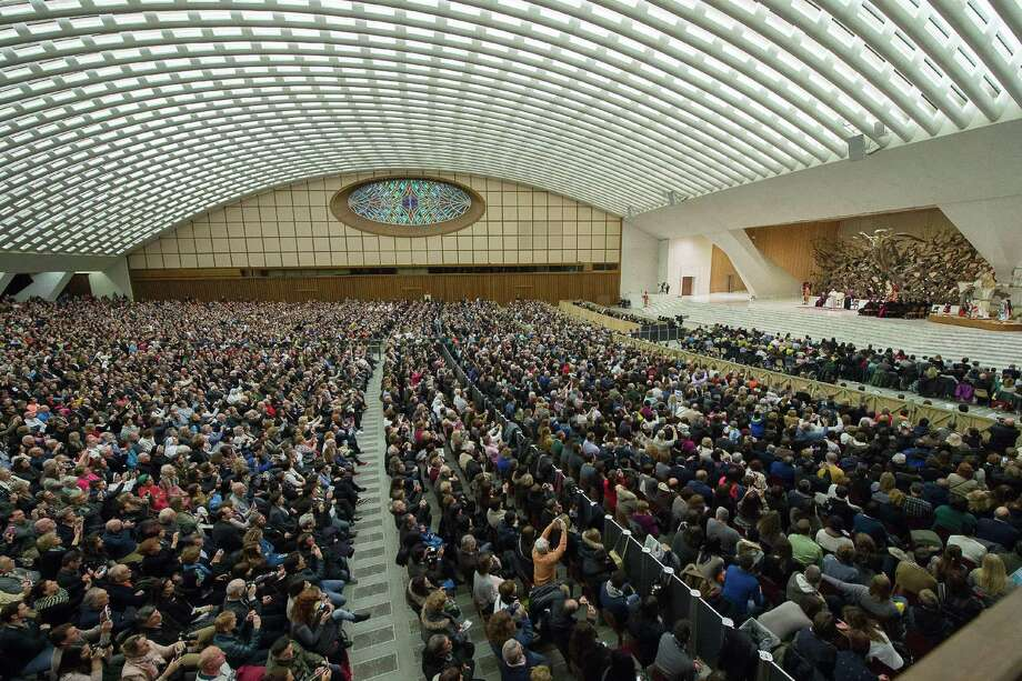 """Pope Francis delivers his speech during his weekly general audience in the Paul VI hall at the Vatican, Wednesday, Jan. 21, 2015. The pontiff is praising big families after saying Catholics don't have to breed """"like rabbits."""" He says big families are a gift and don't cause poverty in the developing world, and that the real cause of poverty is an unjust economic system that idolizes money over people. (AP Photo/L'Osservatore Romano, Pool) Photo: AP / L'Osservatore Romano"""