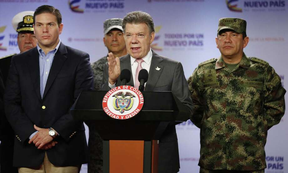 Colombiaís President Juan Manuel Santos announces that at least 26 leftist rebels have been killed in a raid in western Colombia, as he's flanked by Defense Minister Juan Carlos Pinzon, left, and Armed Forces Commander Gen. Juan Pablo Rodriguez, at the presidential palace in Bogota, Friday, May 22, 2015. Colombia's largest rebel group, the Revolutionary Armed Forces of Colombia (FARC), announced they're ending a unilateral cease-fire in response to the military raid on their guerrilla camp. (AP Photo/Fernando Vergara) Photo: AP / AP