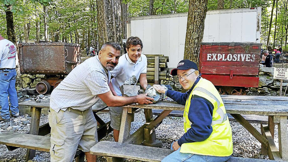 N.F. Ambery photo John Pawloski, president of the Connecticut Museum of Mining & Mineral Science, right, showed some mica rock samples to Steve Palmiotto of Ridgefield and his son Patrick, 16. Photo: Journal Register Co.