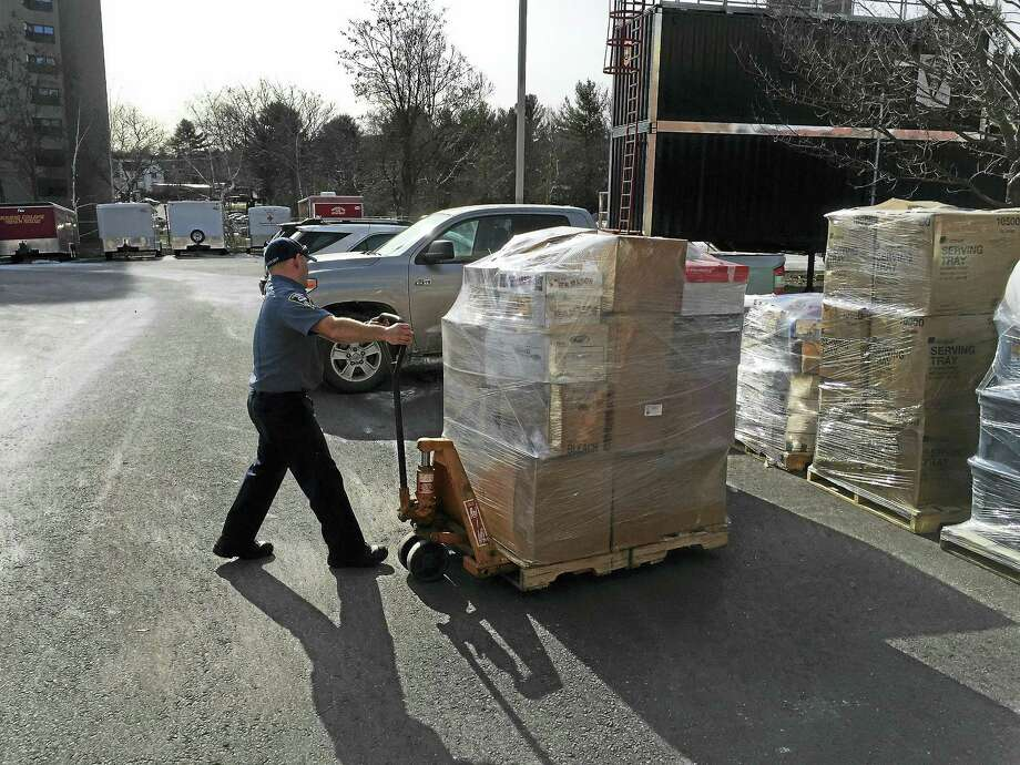 Firefighter Brian Parks maneuvers some of the results of a relief drive for the victims of flooding in Missouri, which were shipped off Friday. Photo: BEN LAMBERT — The Register Citizen